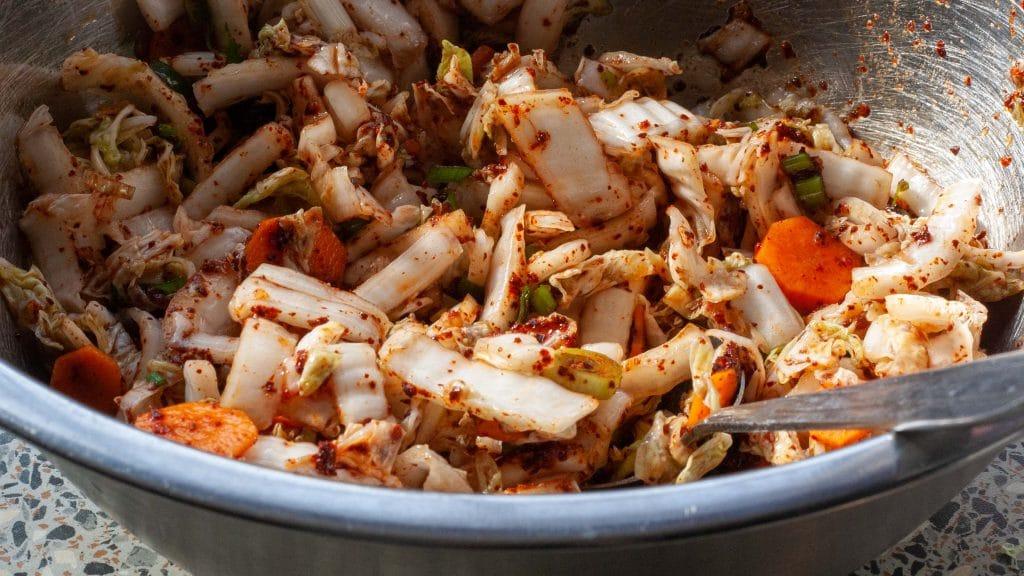 Metalen bak met net gemengde roodgevlekte kimchi van Chinese kool met plakjes wortel en lente-ui