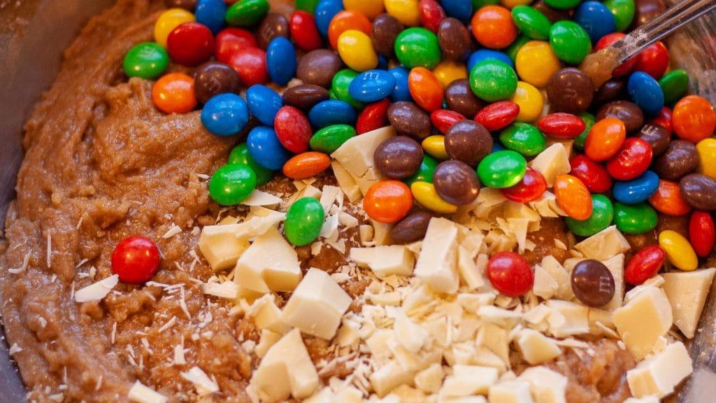 Bruin, zacht koekjesdeeg met M&Ms en stukjes witte chocola erop