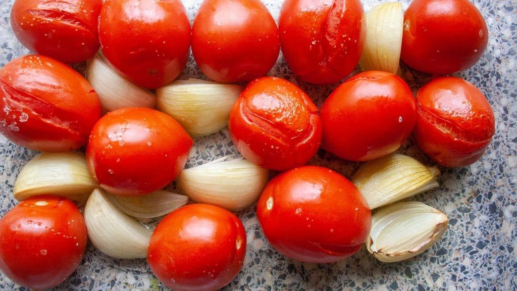 Geroosterde tomaten met gebarsten velletjes en parten geroosterde ui