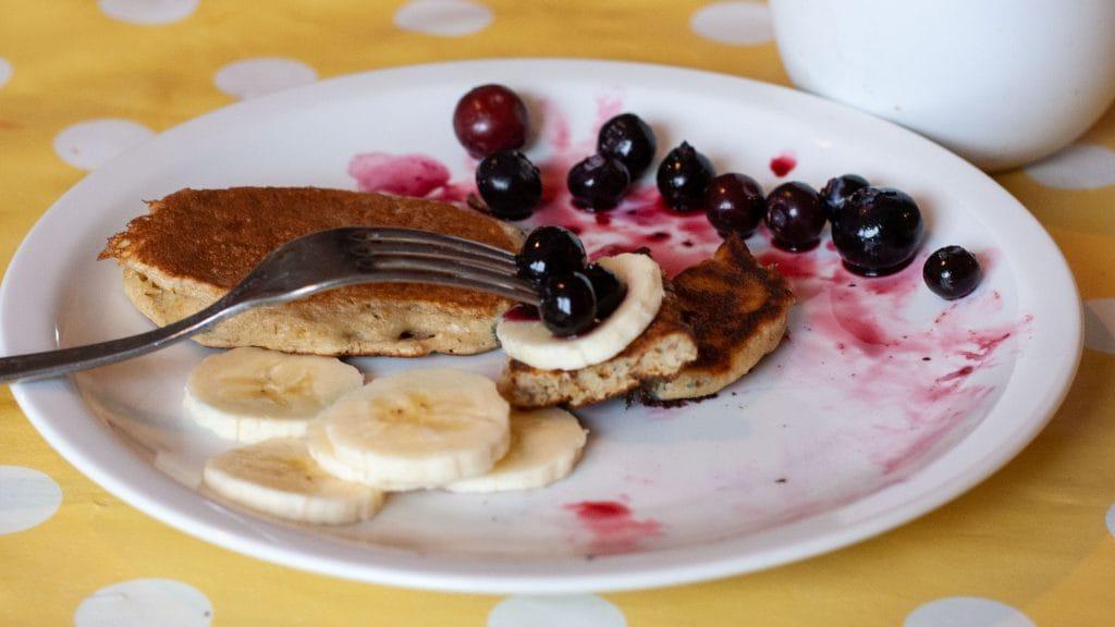 Wit bord met vork erop met daaraan een plakje banaan, twee blauwe bessen en een stukje pannenkoek
