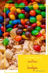 veel M&Ms en wat witte chocolade stukjes op een ondergrond van bruin deeg. Daaronder een tekstvak met de woorden M&M koekjes Amerikaans recept