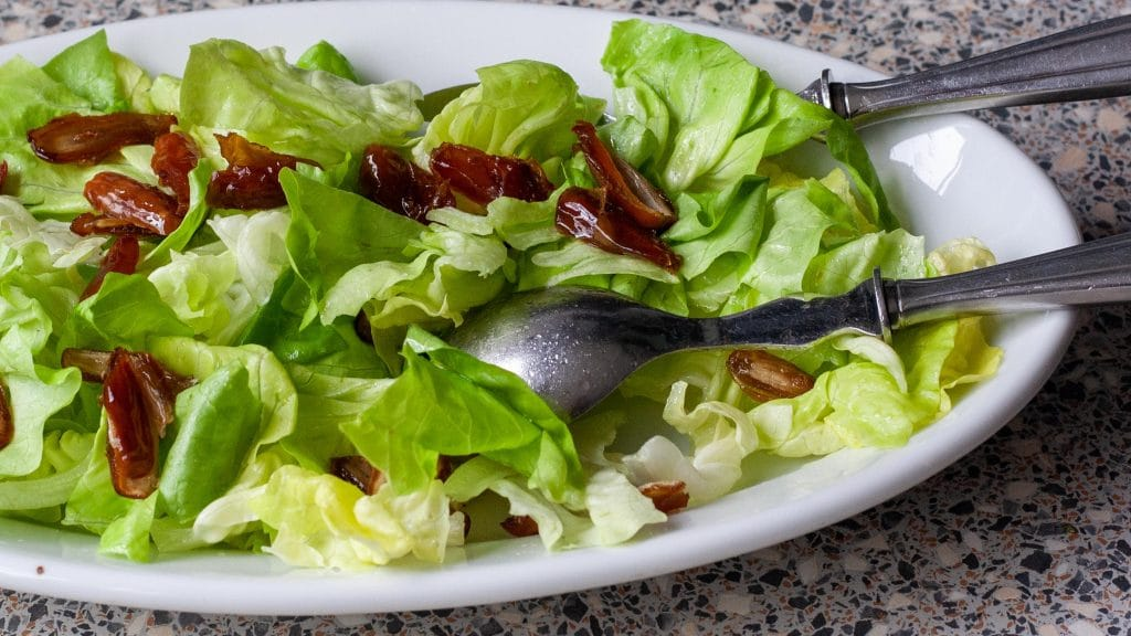Groene salade met halve dadels op witte schaal