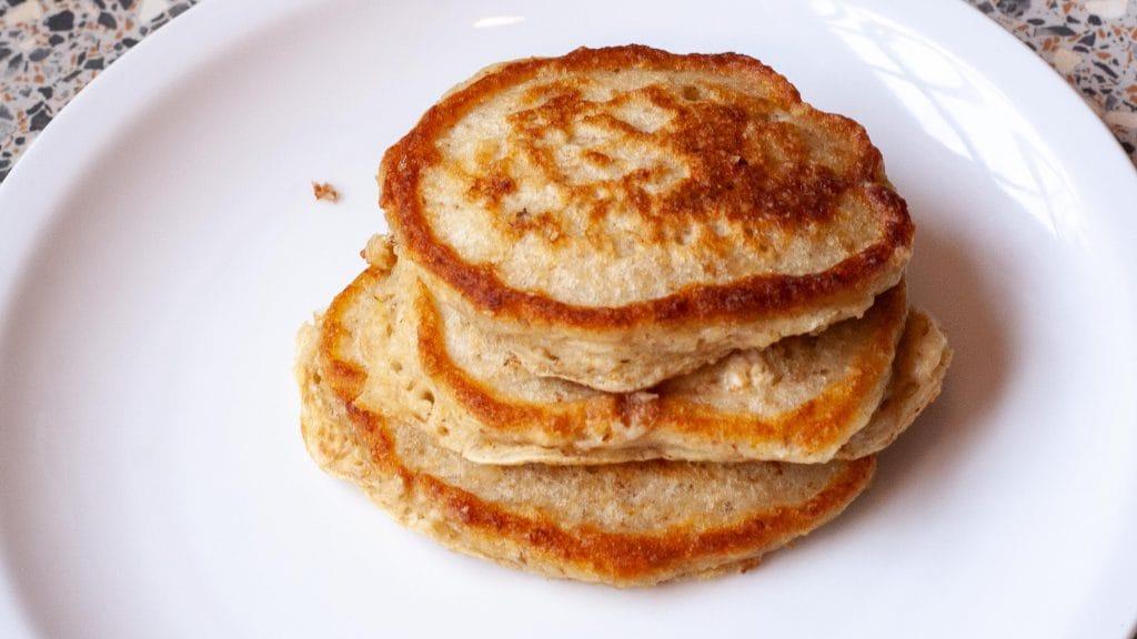 Wit bordje met stapeltje van drie pannenkoekjes met goudbruine randjes