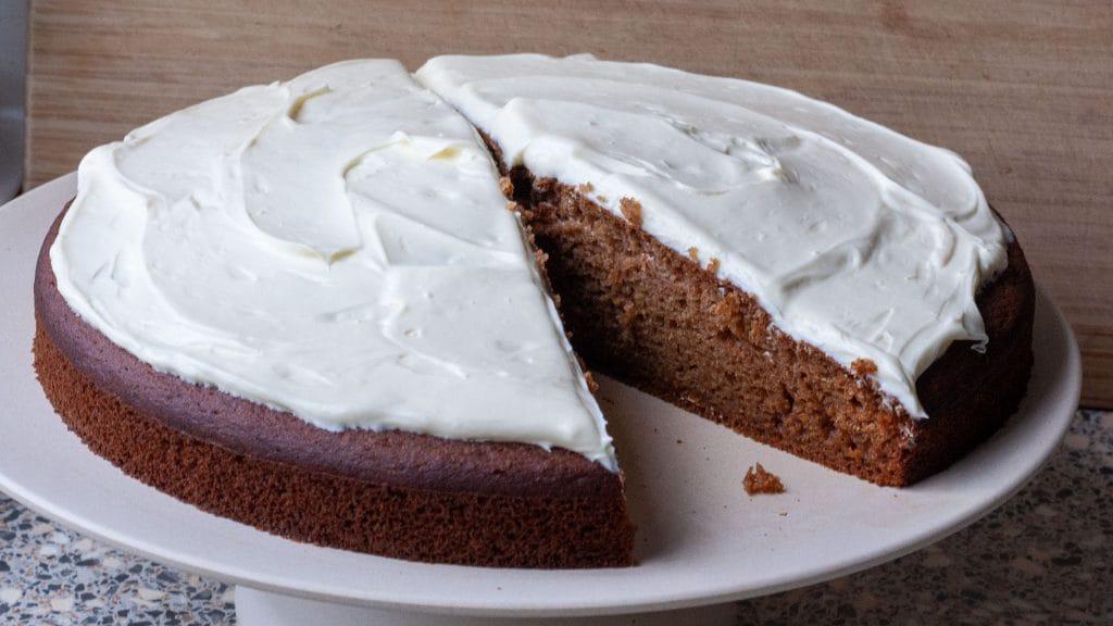 Door de helft gesneden bruine cake met een wit romig laagje erop en één punt eruit gesneden