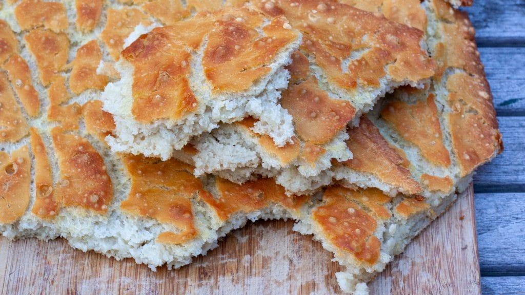 Gescheurde stukken goudbruin, plat brood op een plank
