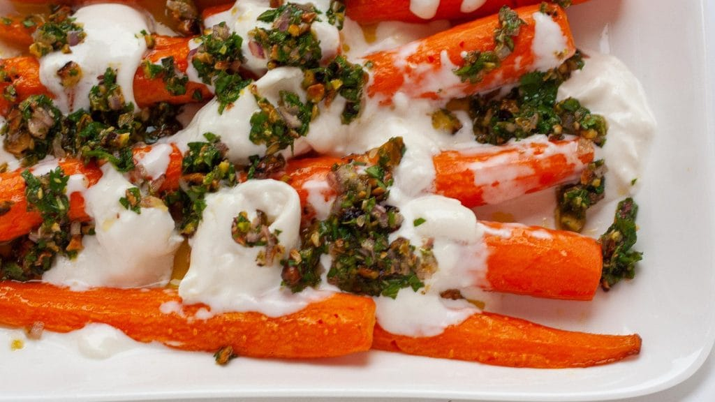 Close up van worteltjes met veel burrata en wat saus van groene kruiden