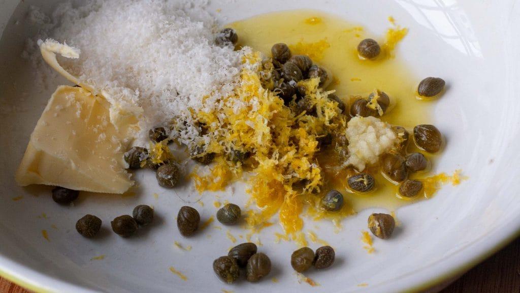 Witte schaal met kappertjes, olijfolie, citroenrasp, geraspte parmezaan en een klontje boter