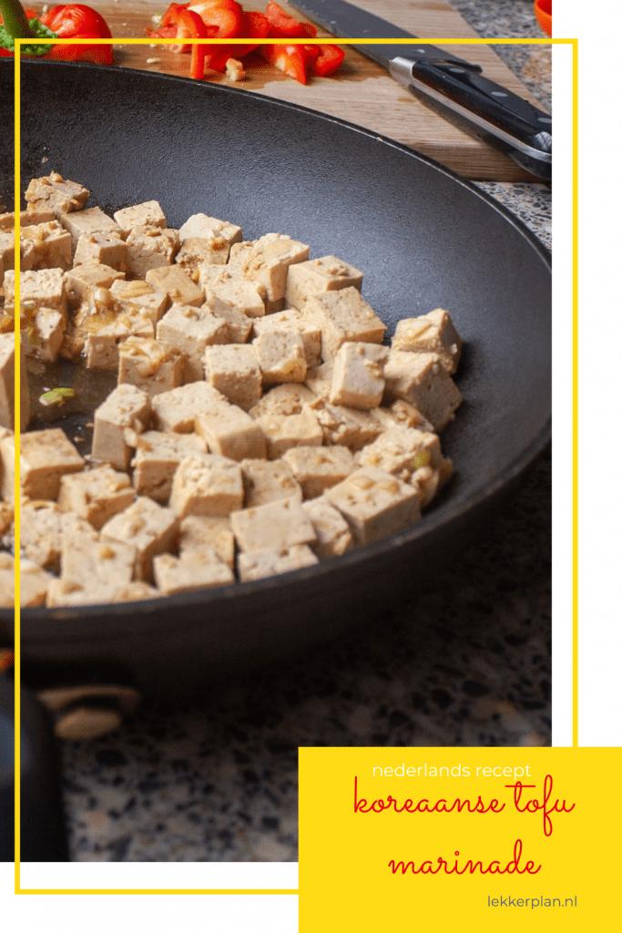Zwarte koekenpan met blokjes lichtbruine, rauwe tofu. Daaronder een tekstvak met de woorden Koreaanse tofu marinade Nederlands recept