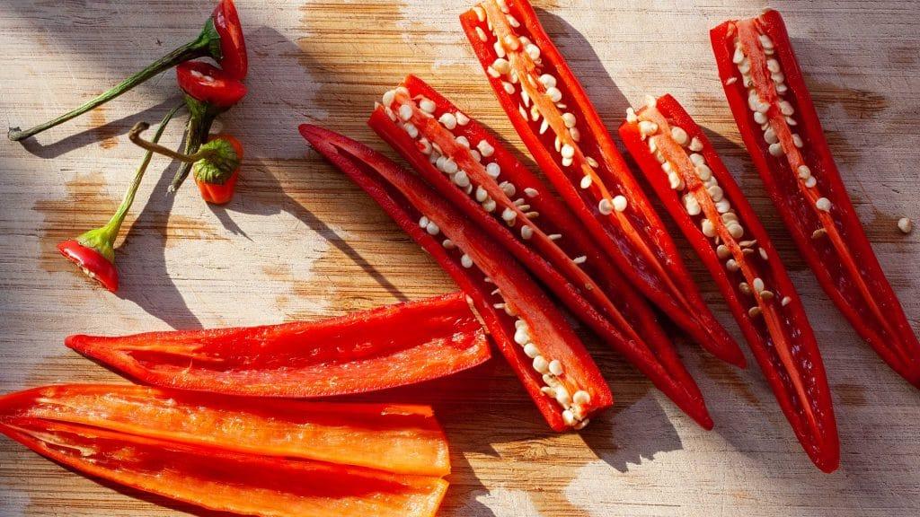 Plankje met gehalveerde rode pepers, waarvan er twee geen zaadjes en zaadlijsten meer hebben
