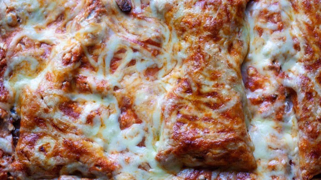 Close-up van de bovenkant van een lasagna met rode saus en slierten gesmolten kaas.
