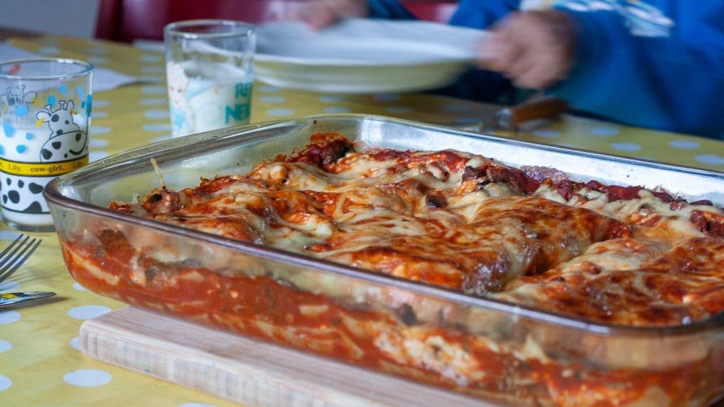 Schaal lasagna schuin van voren gefotografeerd met op de achtergrond een kind dat zijn bord optilt