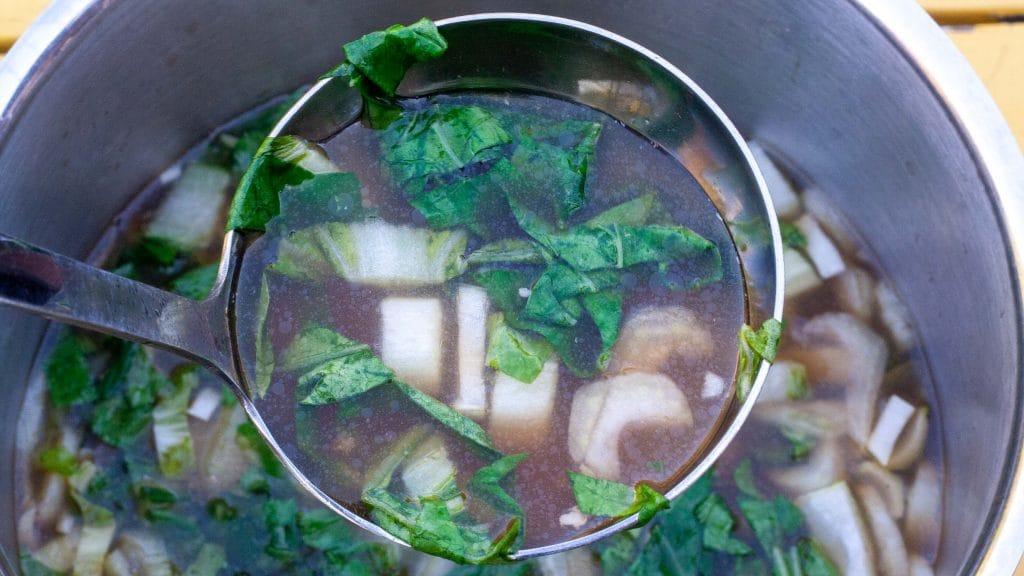 Pan soep met witte en groene stukjes paksoi