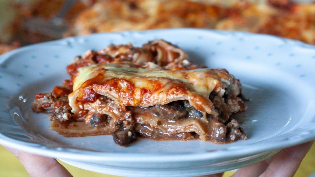 Bord met een stukje lasagna, met laagjes pasta met losse  gehaktsaus ertussen. Je ziet wat stukjes champignon en de bovenkant is bedekt met gesmolten kaas.