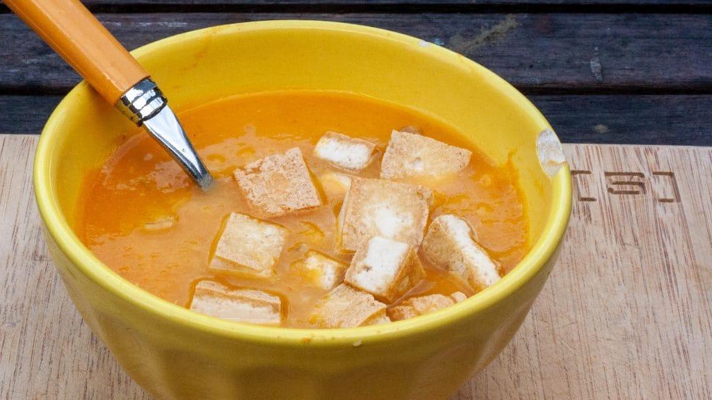 Geel kommetje feloranje soep met blokjes goudbruin gebakken tofu