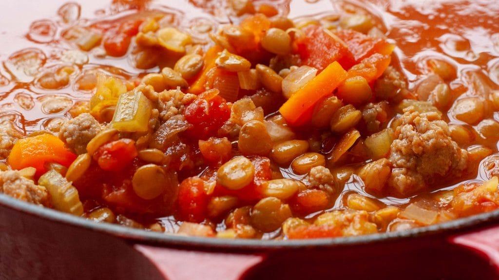 Close-up van linzen met stukjes wortel en bleekselderij in rode soep met stukjes tomaat