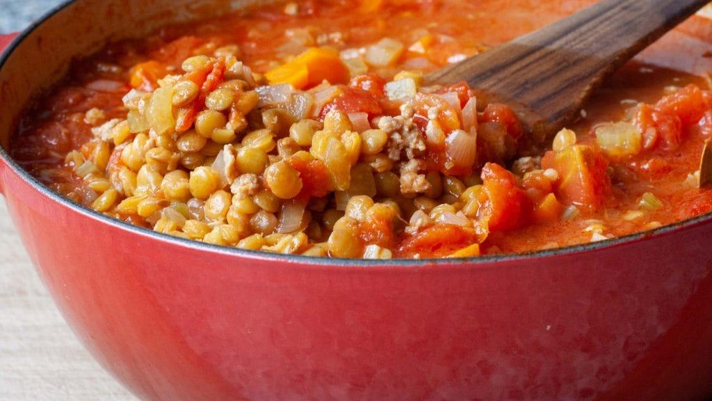 Pan met linzen in tomatensoep met worst en stukjes tomaat