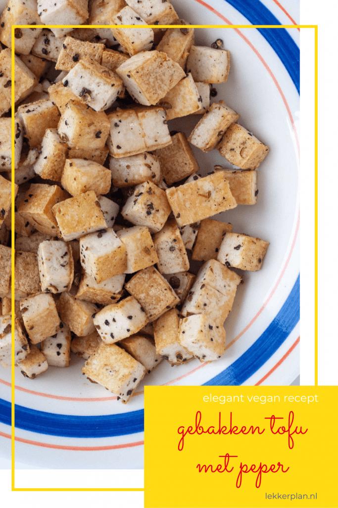 """Close-up van blokjes goudbruine tofu met roze en zwarte peperspikkels. Daaronder de een tekstvak met de woorden """"gebakken tofu met peper, elegant vegan recept"""""""