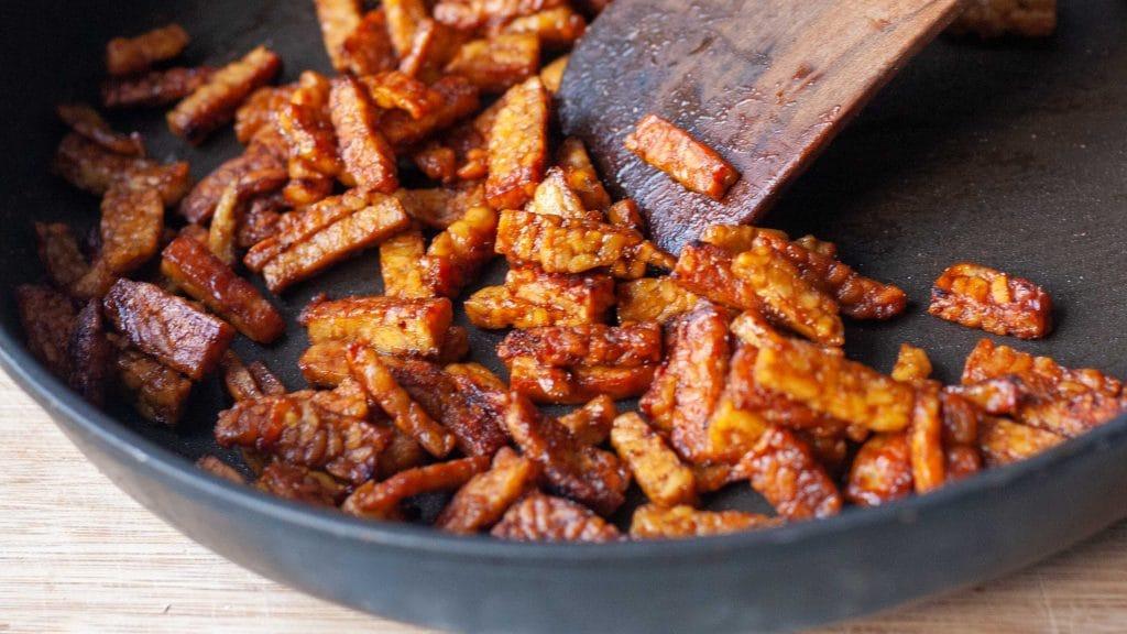 Grijze koekenpan met oranje-bruine dunne reepjes tempeh