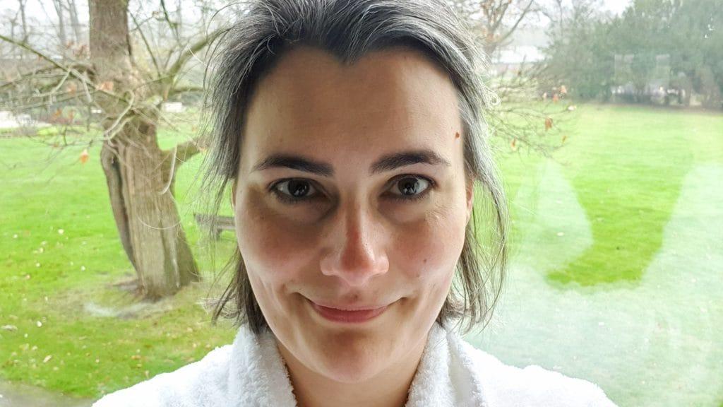 Glimlachend hoofd met badjas eronder en op de achtergrond een groen grasveld