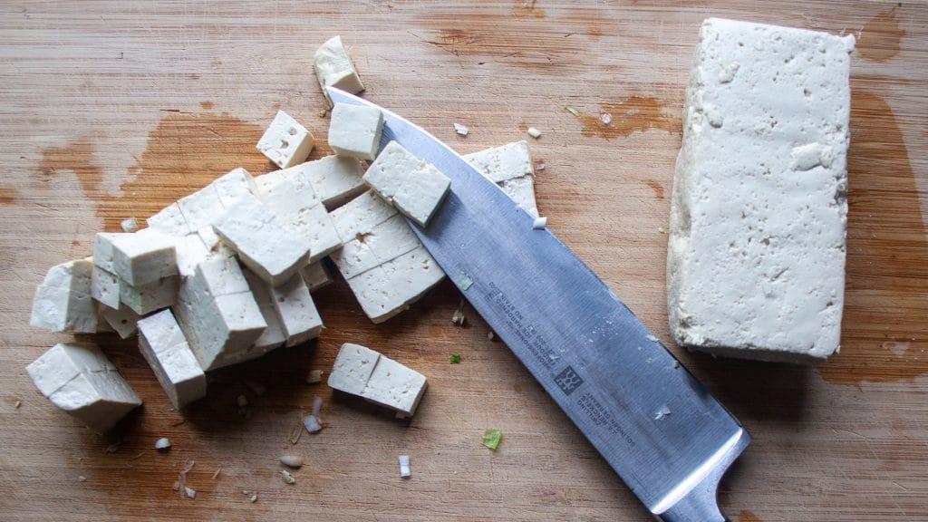 Rauwe tofu in blokje op een snijplank met een groot mes ernaast