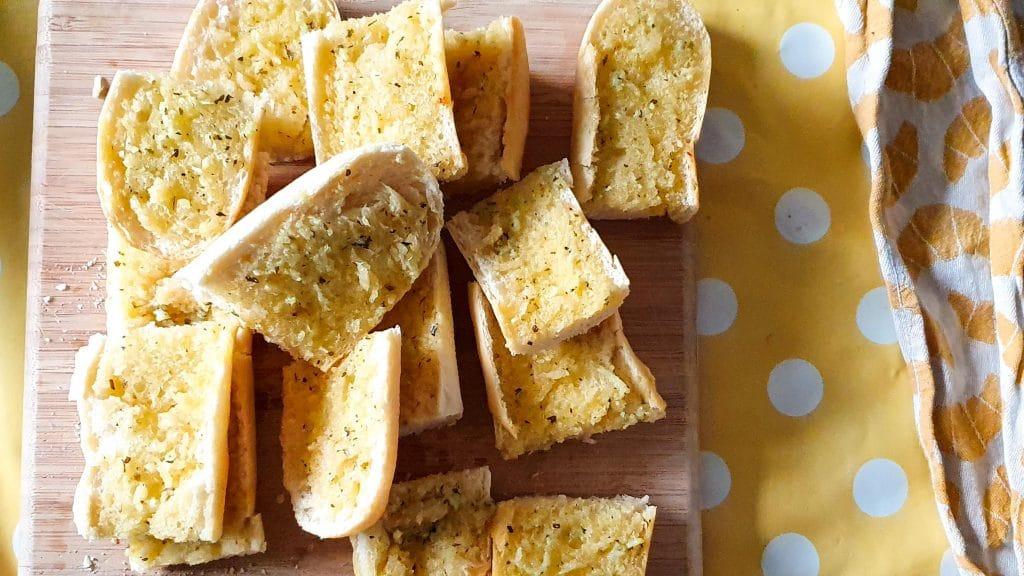 Plank met stukjes  geroosterd brood met knoflookboter