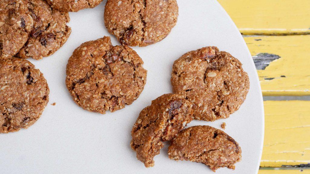 Van boven gefotografeerde chocolate chip koekjes met gebarsten oppervlak. Je ziet gesmolten chocola en stukjes noot in het deeg.