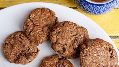 Goudbruine koekjes op een wit bord met een kop thee ernaast